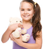 Het leuke meisje borstelt haar teddybeer Stock Afbeeldingen