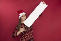 Het leuke meisje die een Kerstmishoed dragen houdt een plaats voor de advertentie stock foto