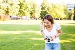 Het leuke meisje die in park terwijl het nemen van foto's met haar kwam glimlachen royalty-vrije stock fotografie