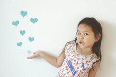 Het leuke meisje die velen tonen trekt hartvorm blazend in de lucht Royalty-vrije Stock Afbeeldingen