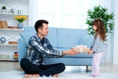 Het leuke meisje, dochter, zuster geeft een giftdoos aan jonge papavader of broer Allebei glimlachen Vaderdagvakantie concep stock fotografie