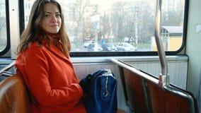 Het leuke meisje in een oranje laag en het dragen van een blauwe zak gaat in openbaar vervoer Het brunette kijkt door het tramven stock videobeelden