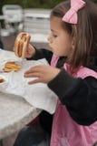 Het leuke meisje eet hamburger met aardappelzitting in koffie outd Stock Fotografie