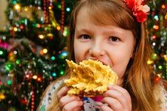 Het leuke meisje eet het nieuwe jaar van cakesakotis en vrolijke Kerstmisachtergrond Stock Fotografie