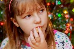 Het leuke meisje eet het nieuwe jaar van cakesakotis en vrolijke Kerstmisachtergrond Stock Foto