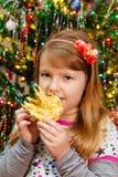Het leuke meisje eet het nieuwe jaar van cakesakotis en vrolijke Kerstmisachtergrond Stock Afbeeldingen