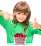 Het leuke meisje eet kersen die de duim omhoog zucht tonen royalty-vrije stock afbeelding
