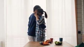 Het leuke meisje en de kerel drinken thee in en dan van kussend na ontbijt dansen uitdrukkend gevoel en keuken die genieten stock video