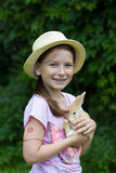 Het leuke meisje glimlachen, die een klein beige Konijntje houden stock foto's
