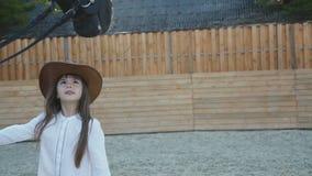 Het leuke meisje in hoed komt en streelt zwart merrie` s hoofd stock video