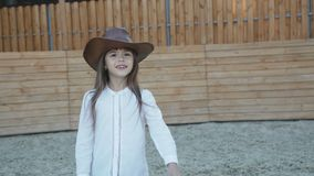 Het leuke meisje in hoed loopt en stelt met glimlach op de renbaan stock video