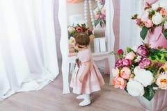 Het leuke meisje kijkt in de spiegel stock fotografie