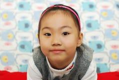 Het leuke meisje kijkt omhoog met een glimlach. Stock Fotografie