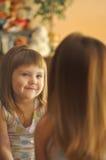 Het leuke meisje kijkt in spiegel het lachen Weinig schoonheid Stock Afbeelding