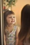 Het leuke meisje kijkt in spiegel het lachen Weinig schoonheid Stock Afbeeldingen