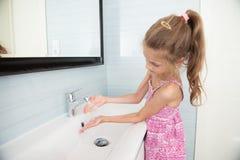 Het leuke meisje in kleding wast haar indient wasbak in heldere badkamers royalty-vrije stock foto's