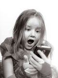 Het leuke meisje kleedde zich in baltoga het spelen met smartphone royalty-vrije stock fotografie