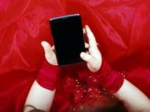 Het leuke meisje kleedde zich in baltoga het spelen met smartphone stock afbeelding