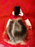 Het leuke meisje kleedde zich in baltoga het spelen met smartphone stock foto's