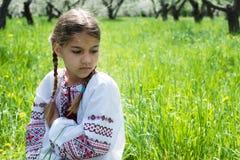 Het leuke meisje kleedde zich in borduurwerk in de tuin royalty-vrije stock afbeeldingen