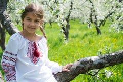 Het leuke meisje kleedde zich in borduurwerk in de tuin royalty-vrije stock afbeelding