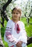 Het leuke meisje kleedde zich in borduurwerk in de tuin royalty-vrije stock fotografie
