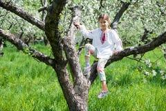 Het leuke meisje kleedde zich in borduurwerk in de tuin stock foto