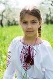 Het leuke meisje kleedde zich in borduurwerk in de tuin stock fotografie