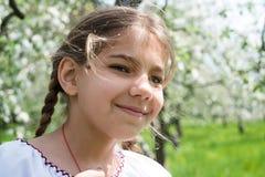 Het leuke meisje kleedde zich in borduurwerk in de tuin stock afbeeldingen