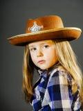 Het leuke meisje kleedde zich in cowboyoverhemd en sheriffhoed Royalty-vrije Stock Afbeeldingen