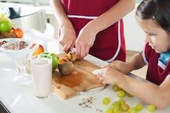 Het leuke meisje koken met haar moeder, gezond voedsel yoghurt Royalty-vrije Stock Foto's