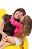 Het leuke meisje kust haar smileymoeder stock foto