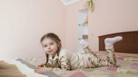 Het leuke meisje legt op bed stock footage