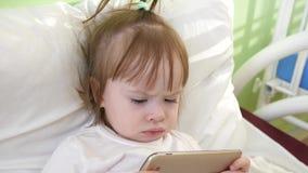Het leuke meisje ligt op bed in het ziekenhuis van kinderen, lettend op grappige beeldverhalen op smartphone royalty-vrije stock foto's