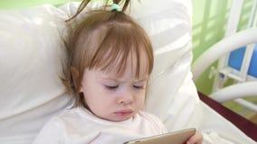 Het leuke meisje ligt op bed in het ziekenhuis van kinderen, lettend op grappige beeldverhalen op smartphone royalty-vrije stock afbeelding