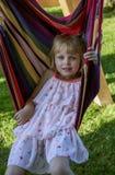 Het leuke meisje ligt in openlucht in een hangmat, heeft een rust in de tuin Stock Afbeelding