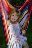 Het leuke meisje ligt in openlucht in een hangmat, heeft een rust in de tuin Stock Foto
