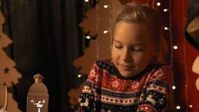 Het leuke meisje met een lantaarn schrijft een brief aan Santa Claus op Kerstavond in langzame motie stock videobeelden