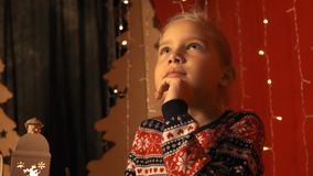 Het leuke meisje met een lantaarn schrijft een brief aan Santa Claus op Kerstavond in langzame motie stock video
