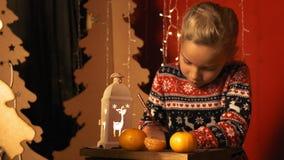 Het leuke meisje met een lantaarn schrijft een brief aan Santa Claus op Kerstavond in langzame motie stock footage