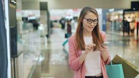 Het leuke meisje met eerlijk haar gebruikt smartphone en glimlacht terwijl het lopen in winkelcomplex met document zakken Interne stock videobeelden
