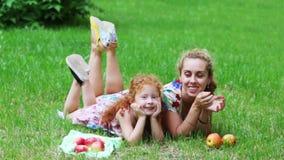 Het leuke meisje met rood haar en haar moeder liggen op gazon stock videobeelden