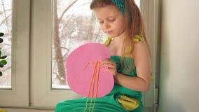 Het leuke meisje naait een roze handtas stock footage