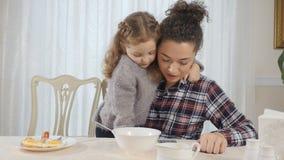 Het leuke meisje omhelst haar moeder en kijkt met haar iets op een smartphone stock videobeelden