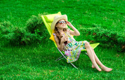 Het leuke meisje ontspant met sap bij stoel op gras Stock Foto's
