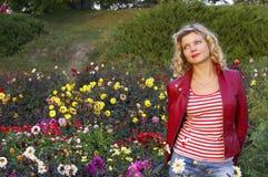 Het leuke meisje op dahlia bloeit weide Stock Afbeelding