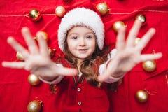 Het leuke meisje op rode achtergrond zette haar voorwaartse handen Stock Fotografie