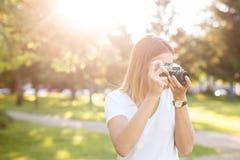 Het leuke meisje op zonnige dag in parkeren die foto's met analogon nemen kwam stock afbeelding