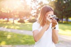 Het leuke meisje op zonnige dag in parkeren die foto's met analogon nemen kwam royalty-vrije stock foto's