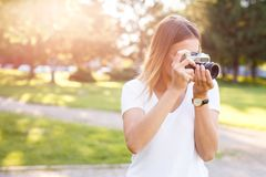 Het leuke meisje op zonnige dag in parkeren die foto's met analogon nemen kwam royalty-vrije stock afbeeldingen